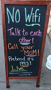 foto di una lavagna all'entrata di un bar, con le scritte NO WiFi. Talk to each other! Call your mom! Prentend it's 1993! Live!